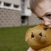 Boy with Black Eye Hugging Teddy Bear