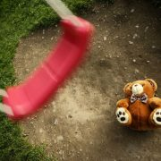 Fallen Teddy Bear Lying In The Swing Set Dirt