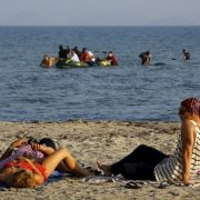 Tourists lie on beach as migrants approach after crossing from Turkey to Greece on the island of Kos
