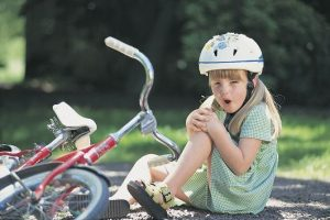 Girl with skinned knee from bike accident