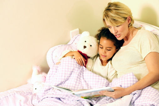 Mother reading daughter bedtime story
