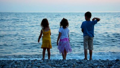 stock-footage-kids-throwing-pebbles-to-sea-standing-in-pebble-beach