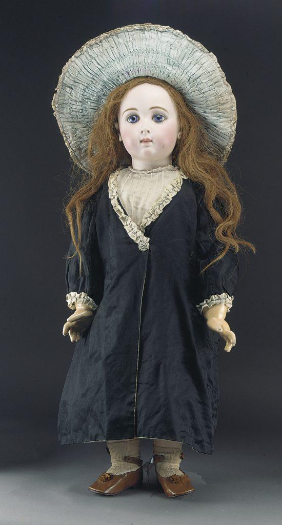 Η Jumeau Carrier-Belleuse Triste είναι μια παιδική κούκλα σε εξαιρετική κατάσταση με μεγάλα μπλε γυάλινα μάτια, σκιασμένα βλέφαρα, τρυπημένα αυτιά, ελαφρώς βαμμένες βλεφαρίδες με πινελιές στην άκρη και στόμα μισάνοιχτο. Έχει περούκα με μακριά ξανθά μαλλιά και χρονολογείται περίπου το 1880. Το 1879 ανατέθηκε στον Albert-Ernest Carrier-Belleuse, το γλύπτη του Γάλλου αυτοκράτορα, να κατασκευάσει ένα κεφάλι κούκλας που θα μπορούσε να χρησιμοποιηθεί είτε από αγόρι είτε από κορίτσι. Ο Carrier-Belleuse θεωρείται ότι χρησιμοποίησε ως μοντέλο ένα πορτρέτο του βασιλιά Ερρίκου της Ναβάρας όταν ήταν τεσσάρων ετών και το σχέδιο έγινε γνωστό ως Jumeau Triste. Αυτή η κούκλα ανήκε σε μία από τις αδελφές Evelyn και Saphia Oakey, που ζούσαν στη Γαλλία όταν ήταν μικρές. Ο πατέρας τους ήταν ο εφευρέτης του σμυριδόπανου και ξεκίνησε μια επιχείρηση γνωστή ως English Abrasives στο Wellington Mills, νότια του σταθμού Waterloo, η οποία υπήρχε μέχρι περίπου πριν από 25 χρόνια.
