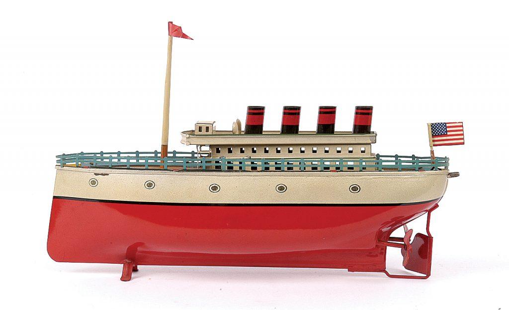 Ένα τσίγκινο πλοίο Arnold 4-Funnel Liner, ζωγραφισμένο, με κόκκινη γάστρα, με φινιστρίνια, φουράγα, λιθογραφημένο κατάστρωμα και κουρδιστή μηχανή. Χρονολογείται περίπου το 1930. Αντιπροσωπεύει τη χρυσή εποχή των πολυτελών πλοίων και των κρουαζιερόπλοιων, πριν διαδοθούν τα αεροπορικά ταξίδια.