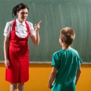 teacher-in-red-and-white-blouse-pointing-finger-at-little-boy
