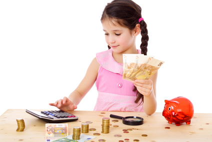 Little girl at the table counts money, isolated on white
