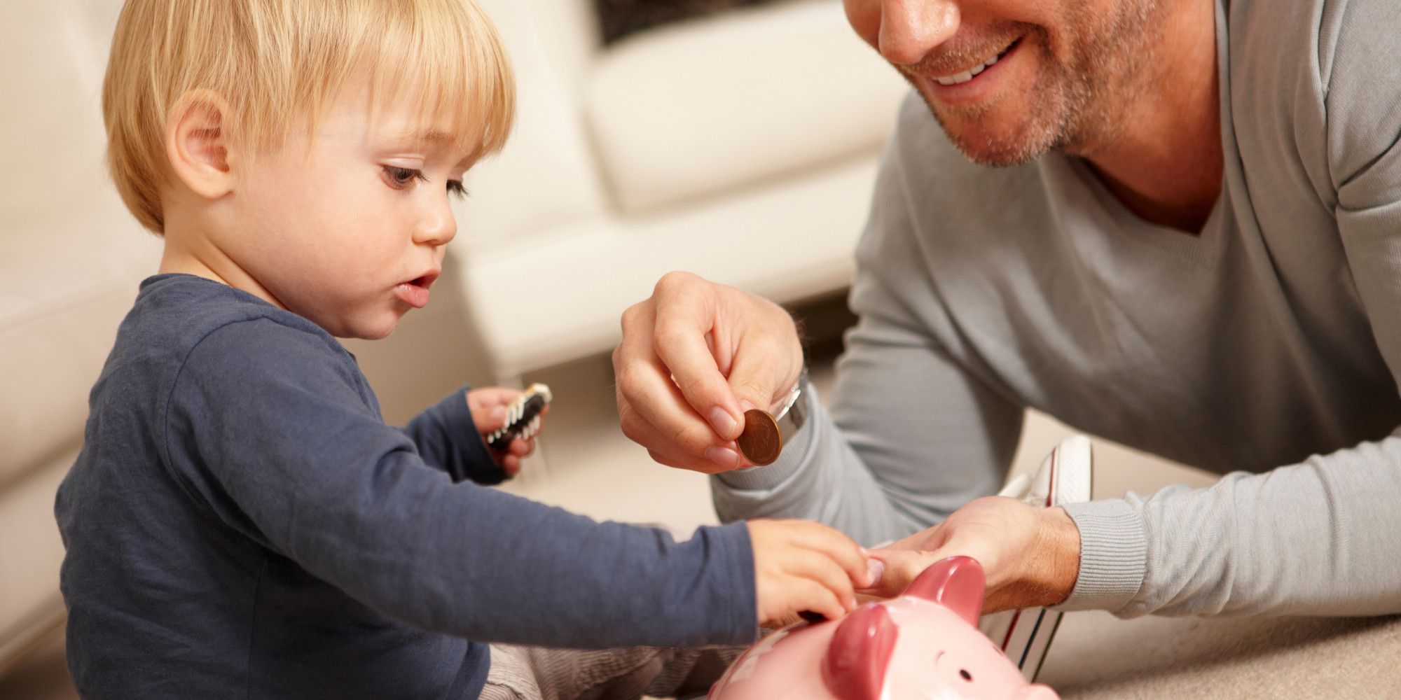 Father and son putting coins in piggy bank