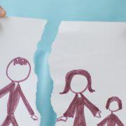 Girl holding drawing of split family
