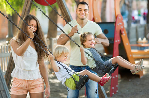 parents-push-children-on-swings-playground