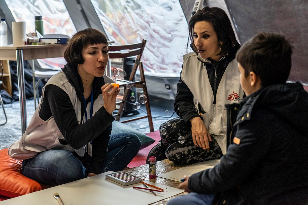 MSF psychologist Danai Papadopouloy, with cultural mediator Marjan Dana Abidian, in session with a minor from Afghanistan during a mental health consultation outside Moria camp on Lesbos island, Greece. Among those referred to our specialised mental health services, for children between the ages of 1-18, our patients present with changes in behaviour such as aggressiveness or withdrawal, stopping eating, nightmares, bed-wetting, panic and anxiety, developmental regression, as well as self-harm, suicidal ideation and suicide attempts.