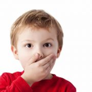 Little boy with hand over his mouth.