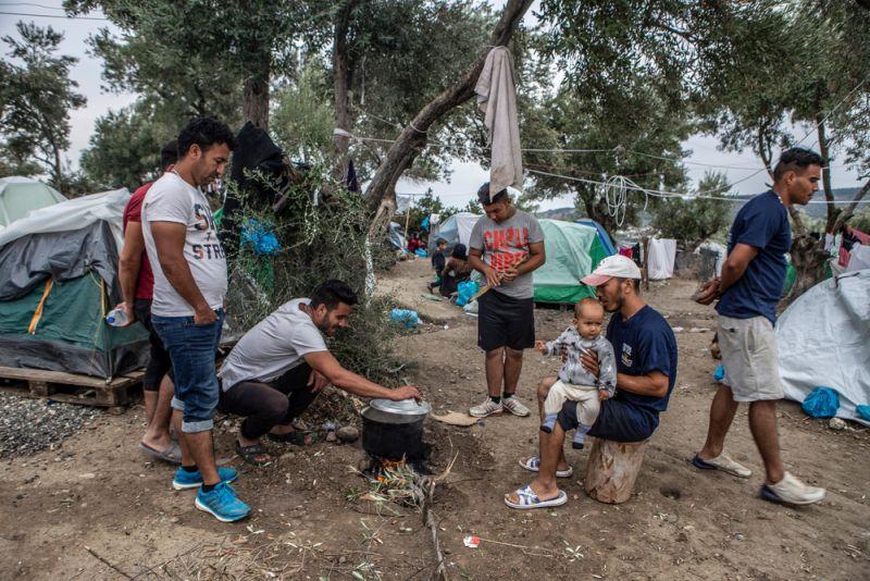 Μια ομάδα Αφγανών μαγειρεύει. Οι άνθρωποι στη Μόρια περιμένουν 2-3 ώρες στην ουρά για να πάρουν το φαγητό που διανέμεται. Μετά την αύξηση των αφίξεων, συχνά το φαγητό δεν φτάνει για όλους.