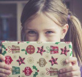 220469-675x450-Little-girl-holding-Christmas-present